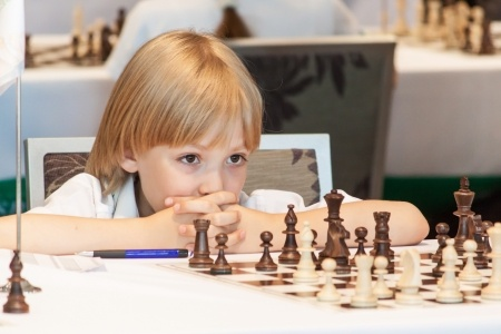 20487182 - young boy playing chess on the competitions