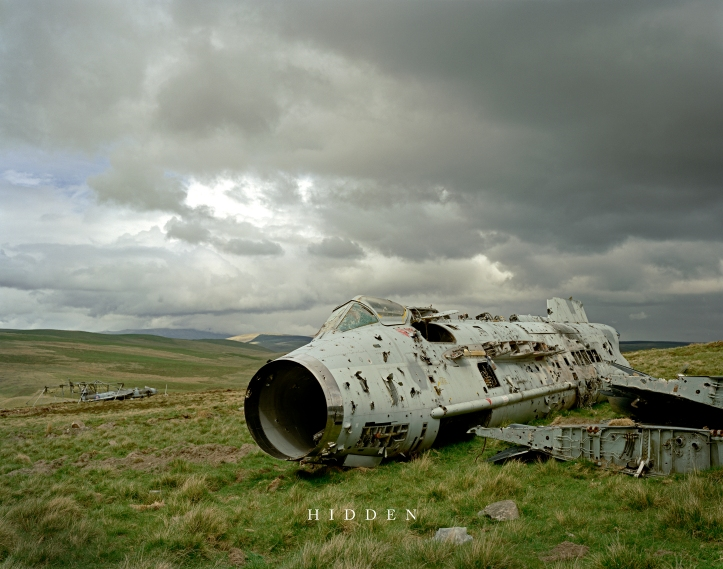The ruined wreck of an aircraft in a field with mountains and greay clouds in the behind